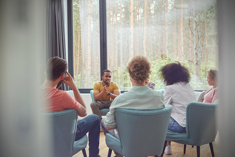 A diverse group sites in blue chairs talking in group therapy session