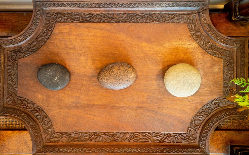 Three stones sit side by side on a wooden carved tray